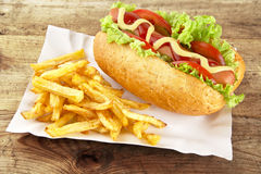 Classic hotdog with chips on tray on plank Royalty Free Stock Photography