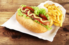Classic hotdog with chips on tray on plank Royalty Free Stock Image