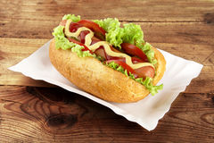 Classic hotdog with chips on tray on plank Royalty Free Stock Photos