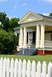 Classic house. Classic older home with white picket fence, porch with columns; set against blue sky royalty free stock photography