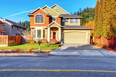 Classic house with garage, driveway, and grassy front yard. Stock Image