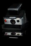 Classic Instant Polaroid Camera. Classic black vintage instant polaroid camera isolated on black background Stock Photo