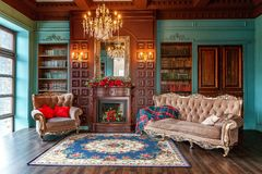 Classic Interior of home library. Luxury classic interior of home library. Sitting room with bookshelf, books, arm chair, sofa and fireplace. Clean and modern royalty free stock photography