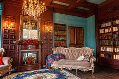 Classic Interior of home library. Luxury classic interior of home library. Sitting room with bookshelf, books, arm chair, sofa and fireplace. Clean and modern stock images