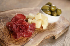 Classic italian antipasti, breasola. olives and parmesan on olive board Stock Images
