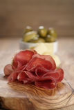 Classic italian antipasti, breasola. olives and parmesan on olive board Royalty Free Stock Image