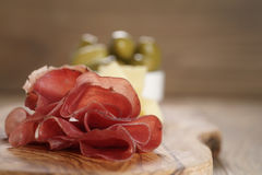 Classic italian antipasti, breasola. olives and parmesan on olive board Royalty Free Stock Photo
