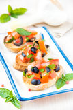 Classic Italian appetizer bruschetta with tomato, basil and blac Stock Photos