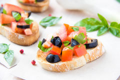 Classic Italian appetizer bruschetta with tomato, basil and blac. K olives on table Royalty Free Stock Images