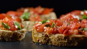 Classic Italian bruschetta, tomato, garlic and parsley on toasted bread. Rotates on a turntable, seamless loopable stock video footage