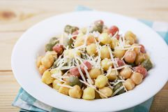 Classic italian lunch with Gnocchi with sage, butter and Parmesa. Cooked colored gnocchi with sage, butter and Parmesan cheese in white plate on rustic natural stock photos