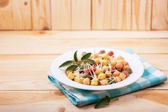 Classic italian lunch with Gnocchi with sage, butter and Parmesa. Cooked colored gnocchi with sage, butter and Parmesan cheese in white plate on rustic natural stock photography