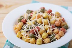 Classic italian lunch with Gnocchi with sage, butter and Parmesa. Cooked colored gnocchi with sage, butter and Parmesan cheese in white plate on rustic natural royalty free stock photography