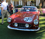 Classic italian race car front view. Classic 1950s red italian race car number 36 front view. silver roof and red body. Ferrari 250 gt boano coupe around people royalty free stock image