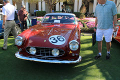 Classic italian race car front view. Classic 1950s red italian race car front view. white roof and red body. Ferrari 250 gt boano coupe around onlookers. face royalty free stock image