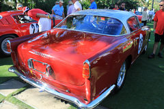 Classic italian race car side rear view. Classic 1950s red italian race car rear quarter view. white roof and red body. Ferrari 250 gt boano coupe around people stock images