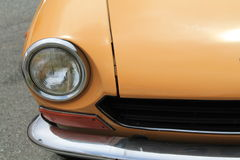 Classic italian sports car headlamp. Classic 1970s orange fiat 124 spider front corner. headlamp, hood and grille. Italian  car fiat freakout event 2012 in Stock Photo