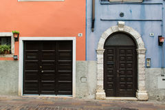 Classic Italy entrance doors on colorful wall. Two classic Italian doors on walls painted blue and orange stock images