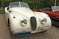 Classic jaguar automobile. A classic off-white open-top jaguar automobile standing on gravel stock photos