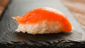 Classic Japanese sushi with salmon, close up view. Close up of one classic Japanese nigiri sushi with fresh salmon served on black slate, close up view. Healthy Stock Photography
