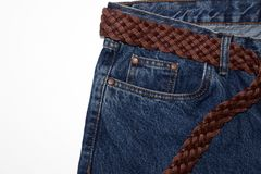 Classic jeans with five pockets close-up. jeans with a woven belt of brown leather and coarse thick threads. vintage blue textured stock image