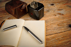 Classic journalist tools. Still life with vintage camera, fountain pen and notebook, a journalism concept Royalty Free Stock Images