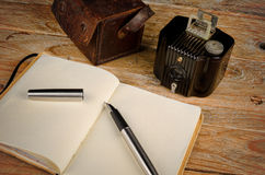 Classic journalist tools. Still life with vintage camera, fountain pen and notebook, a journalism concept Stock Photography