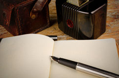 Classic journalist tools. Still life with vintage camera, fountain pen and notebook, a journalism concept Royalty Free Stock Image