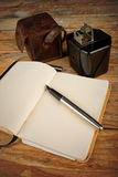 Classic journalist tools. Still life with vintage camera, fountain pen and notebook, a journalism concept Stock Image