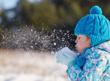 Classic joys of winter. Candid shot of a cute little girl blowing snow flakes from her hands outdoors on a sunny winter's day Stock Photography