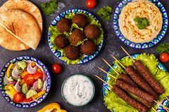 Classic kebabs, falafel and hummus on the plates. Top view Royalty Free Stock Images