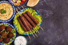 Classic kebabs, falafel and hummus on the plates. Top view, copy space Stock Photo
