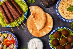 Classic kebabs, falafel and hummus on the plates. Top view Stock Image