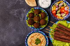 Classic kebabs, falafel and hummus on the plates. Top view, copy space Royalty Free Stock Photo