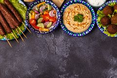 Classic kebabs, falafel and hummus on the plates. Top view, copy space Stock Images