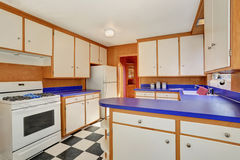 Classic kitchen room interior with white cabinets with blue counter top. Also tile floor. Northwest, USA Royalty Free Stock Photo