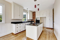 Classic kitchen room interior with white cabinets and dark counter top. Royalty Free Stock Images