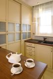 Classic Kitchen with Teapot And Cups. Classic streamline kitchen area of a home. White teapot and two cups of tea are sitting on the counter stock photography