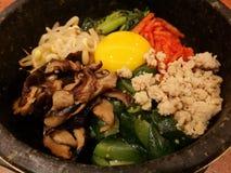 Classic Korea food vegetable Bibimbap hot stone pot,rice carrot,spinach,mushroom,cucumber,seaweed,raw yolk egg,hot spicy chili sau Royalty Free Stock Photos