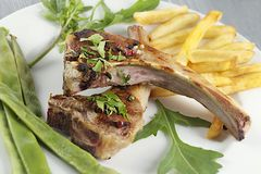 Classic lamb chops. Plate served french fries and green beans royalty free stock images