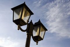 Classic lamppost. Classic black lamppost with two lights against blue sky Royalty Free Stock Photos