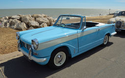 Classic light Blue Triumph Herald open top motor car parked on seafront promenade. Royalty Free Stock Photos