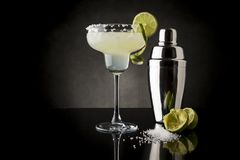 Lime margarita cocktail. Classic lime margarita cocktail with tequila, triple sec, lime juice, crushed ice and some salt on the rim of a glass, decorated with a royalty free stock images