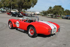 Classic little red sports car. Vintage red Shelby Cobra sporting white racing stripes and a number seventy seven decal, Miami, Florida 2015 Stock Image
