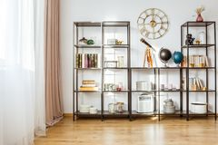 Classic living room with clock. Telescope and globes on the shelf against white wall with gold round clock in classic living room interior Stock Photography