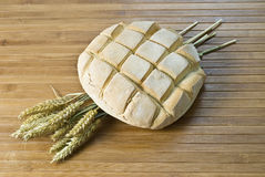 A classic loaf. A classic loaf and some wheat on a bamboo mat Royalty Free Stock Photo