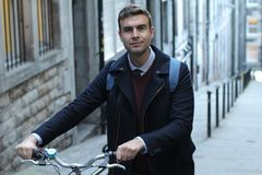 Classic looking man carrying bicycle upstairs.  royalty free stock photography