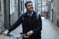 Classic looking man carrying bicycle upstairs.  stock image