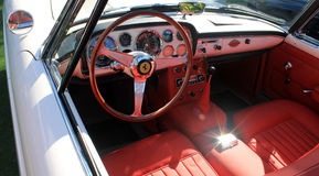 Classic luxury white Ferrari interior. Classic white 1960 luxury Ferrari 250 GT PF Cabriolet Series II sporting white and red interior. outdoors under natural Stock Images