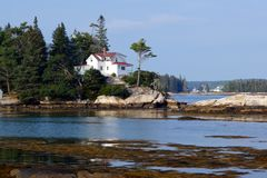 Classic Maine coast view. House built on a bluff overlooking rugged Maine coastal waters. Boothbay Harbor area. Low tide. Late summer stock photos